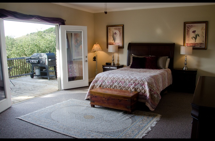 Master bedroom with French doors opening to the large deck with a sunset view