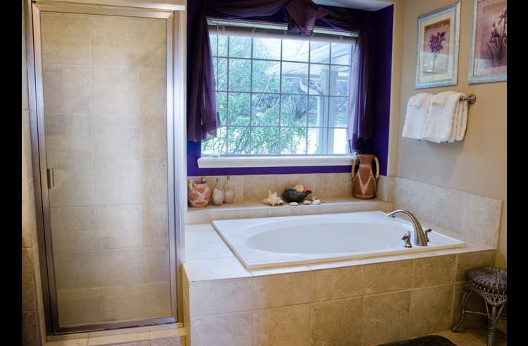 One of two downstairs bathrooms, this spacious master bath has a shower, tub and private toilet room.