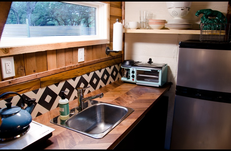 The tiny kitchen features a double hot plate, toaster oven, coffee maker, fridge/freezer and a basic set of dishes and cookware