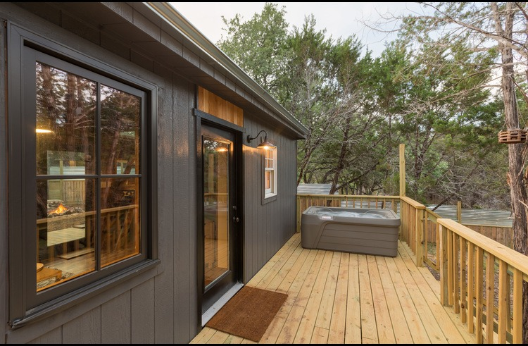 The back deck and two person hot tub overlook the private woods behind the home