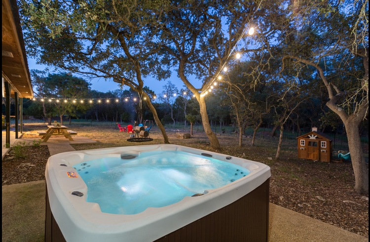 The hot tub is surrounded by private acreage, oaks and twinkle lighting.