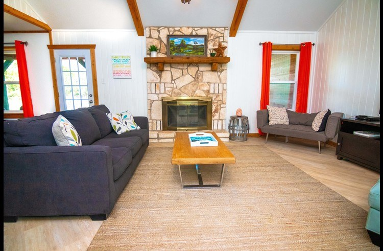 The living area has a queen sleeper sofa, ample seating and a cozy fireplace with high celings.