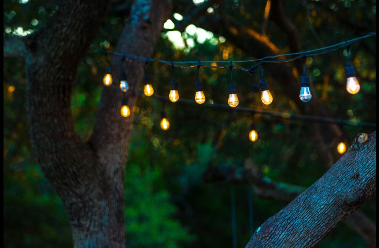 Romantic string lights under the oaks and over the hot tub