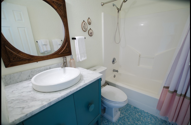 Downstairs bath with whimsical turquoise penny tiles & full tub/shower combo