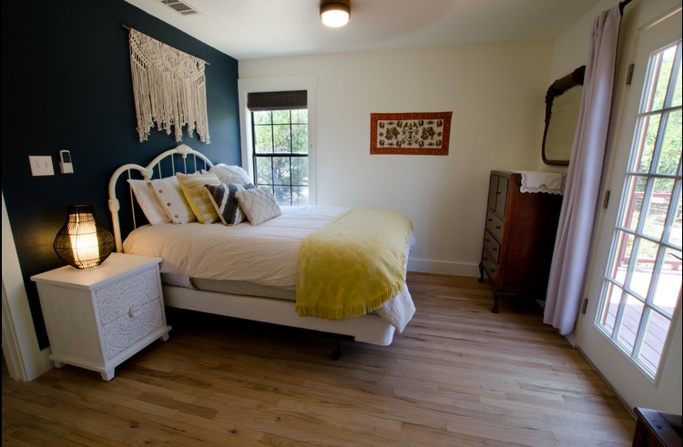 The downstairs bedroom features a queen bed and private door to the deck/hot tub