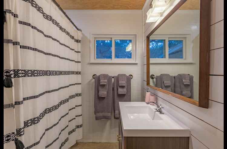 Main house bathroom featuring a combo tub/shower, perfect for kids!