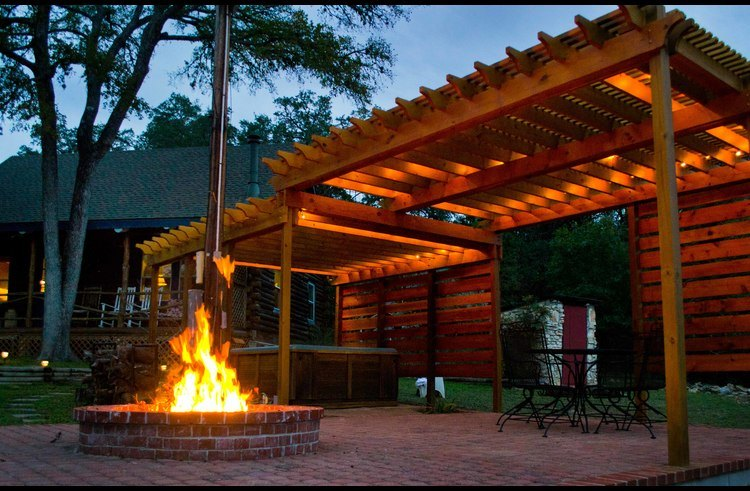 The outdoor veranda features a hot tub, outdoor dining area and fire pit.